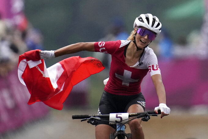 Jolanda Neff of Switzerland celebrates as she crosses the finish lone to win the gold medal during the women's cross-country mountain bike competition at the 2020 Summer Olympics, Tuesday, July 27, 2021, in Izu, Japan. (AP Photo/Christophe Ena)