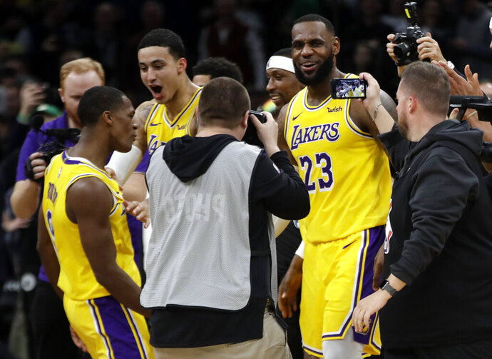 Los Angeles Lakers guard Rajon Rondo, left, celebrates his game-winning shot with teammates Kyle Kuzma, middle, and LeBron James (23) in an NBA basketball game against the Boston Celtics, Thursday, Feb. 7, 2019, in Boston. The Lakers won 129-128. (AP Photo/Elise Amendola)