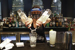 FILE - In this July 1, 2020, file photo, a bartender mixes a drink while wearing a mask and face shield at Slater's 50/50 in Santa Clarita, Calif. Getting children back to school safely could mean keeping high-risk spots like bars and gyms closed. That's the latest thinking from some public health experts. (AP Photo/Marcio Jose Sanchez, File)