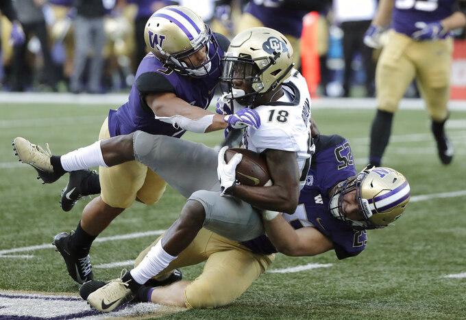 Colorado wide receiver Tony Brown (18) is tackled by linebacker Ben Burr-Kirven, right, and linebacker Joe Tryon, left, during the second half of an NCAA college football game, Saturday, Oct. 20, 2018, in Seattle. Washington won 27-13. (AP Photo/Ted S. Warren)