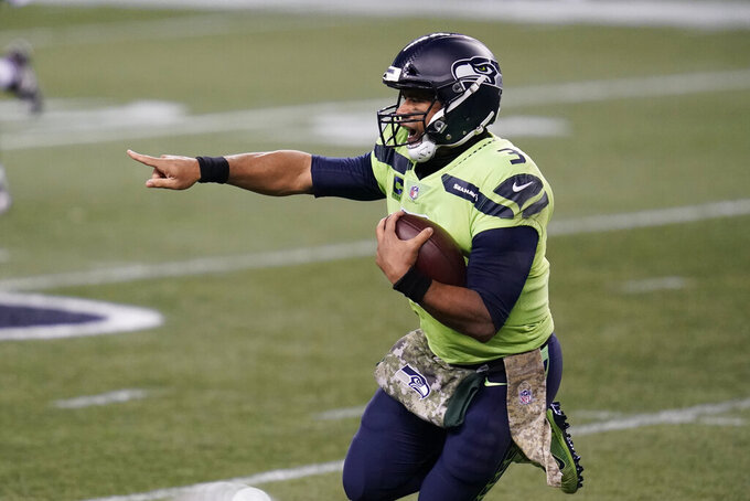 Seattle Seahawks quarterback Russell Wilson gestures as he scrambles against the Arizona Cardinals during the first half of an NFL football game, Thursday, Nov. 19, 2020, in Seattle. (AP Photo/Elaine Thompson)