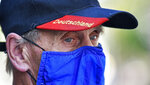 Due to the new coronavirus pandemic a man wears a face mask of the German first division soccer team FC Schalke 04 and a hat with the word reading