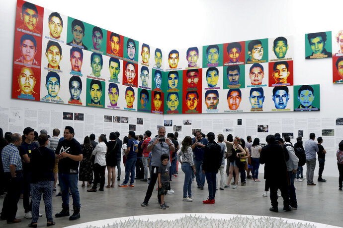 People stand under the portraits of 43 college students who went missing in 2014 in an apparent massacre, by Chinese concept artist and government critic Ai Weiwei at the Contemporary Art University Museum (MUAC ) in Mexico City, Mexico, Saturday, April 13, 2019. Each portrait in the work of art titled
