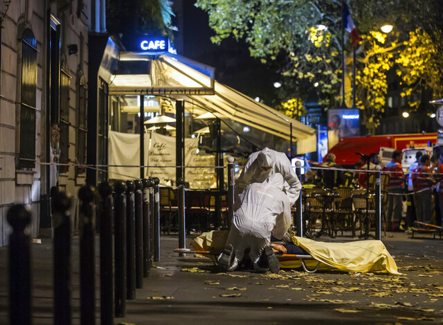 FILE - In this Friday, Nov. 13, 2015 file photo, investigating police officers inspect the lifeless body of a victim of a shooting attack outside the Bataclan concert hall in Paris. French judges investigating the 2015 Islamic State attacks that left 130 people dead in Paris have ordered charges against 20 people on Monday, including a Belgian accused of masterminding the attacks who was held for years in Abu Ghraib prison in Iraq before being freed and returned home. (AP Photo/Kamil Zihnioglu, File)
