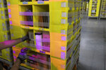 FILE - In this Dec. 5, 2018, file photo Amazon Stower Leo Esparragoza uses colored light to help sort merchandise into pods at the Amazon fulfillment center on Staten Island borough of New York. On Monday, July 15, 2019, the first day of Amazon Prime Day's 48-hour sales event, large retailers, those that generated annual revenue of at least a billion dollars, enjoyed a 64% increase in online sales compared with an average Monday, according to Adobe Analytics, which measures 80 of the top 100 retailers on the web in the U.S. (AP Photo/Mary Altaffer, File)
