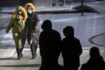 People wearing face masks to protect against the coronavirus walk on an unseasonably cold day at an office and shopping complex in Beijing, Wednesday, Jan. 6, 2021. China's Hebei province is enforcing stricter control measures following a further rise in coronavirus cases in the province, which is adjacent to the capital Beijing and is due to host events for next year's Winter Olympics. (AP Photo/Mark Schiefelbein)