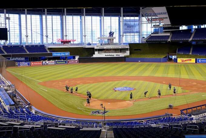 Grounds crew work in an empty Marlins Park before a baseball game between the Miami Marlins and New York Mets, Thursday, Aug. 20, 2020, in Miami. Major League Baseball says the Mets have received two positive tests for COVID-19 in their organization, prompting the postponement of two games against the Marlins. (AP Photo/Lynne Sladky)