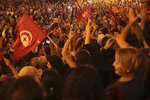 A crowd gathers on Tunis' main avenue, Sunday, Oct. 13, 2019. Tunisian polling agencies are forecasting that conservative law professor Kais Saied has overwhelmingly won the North African country's presidential election. (AP Photo/Mosa'ab Elshamy)