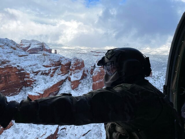 This photo provided by the Arizona National Guard shows a UH-60 Black Hawk crew with the Arizona National Guard during a rescue of three stranded climbers in snow covered Haribo Canyon in Sedona, Ariz. on Tuesday, Jan. 26, 2021. Crews in northern Arizona used a helicopter and a tracked vehicle to rescue a total of five people in two incidents in areas blanketed by heavy snow from a major storm, authorities said. (Maj. Kyle Key/Arizona National Guard via AP)