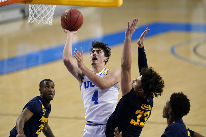 UCLA guard Jaime Jaquez Jr. (4) shoots next to Marquette forward Dawson Garcia (33) during the second half of an NCAA college basketball game Friday, Dec. 11, 2020, in Los Angeles. (AP Photo/Ashley Landis)