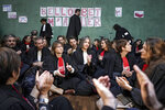 Lawyers sit on the floor in the Lyon court house in Lyon, central France on Tuesday, Jan. 14, 2020, in front of posters referring to French Justice Minister Nicole Belloubet that read: