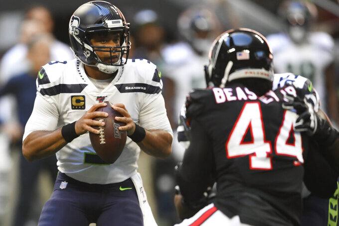 Seattle Seahawks quarterback Russell Wilson (3) works in the pocket as Atlanta Falcons defensive end Vic Beasley (44) pressures during the first half of an NFL football game, Sunday, Oct. 27, 2019, in Atlanta. (AP Photo/John Amis)