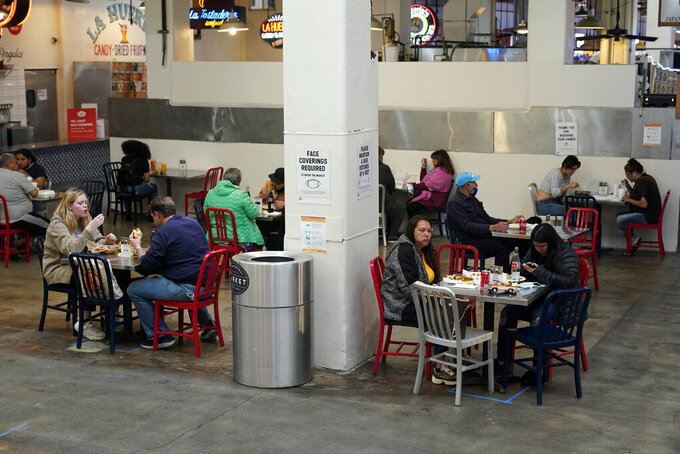 FILE - In this March 17, 2021 file photo Patrons eat lunch in an indoor space at Grand Central Market in Los Angeles. A rapid and sustained increase in COVID-19 cases in the nation's largest county requires restoring an indoor mask mandate even when people are vaccinated, Los Angeles County's public health officer said Thursday, July 15, 2021.(AP Photo/Marcio Jose Sanchez, File)