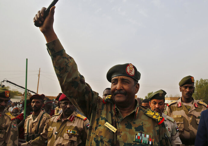 FILE - In this June 29, 2019  file photo, Sudanese Gen. Abdel-Fattah Burhan, head of the military council, waves to his supporters upon his arrival to attend a military-backed rally, in Omdurman district, west of Khartoum, Sudan.  On Wednesday, Aug. 21, 2019, Burhan was sworn in as the leader of a joint military-civilian body, which is to run the country for a little over three years until elections can be held. The official SUNA news agency says Gen. Abdel-Fattah Burhan was sworn in before the country's top judge. (AP Photo/Hussein Malla, File)