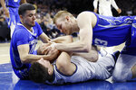 Villanova's Collin Gillespie, center, tries to hang on to a loose ball against Creighton's Marcus Zegarowski, left, and Kelvin Jones during the first half of an NCAA college basketball game, Saturday, Feb. 1, 2020, in Philadelphia. (AP Photo/Matt Slocum)