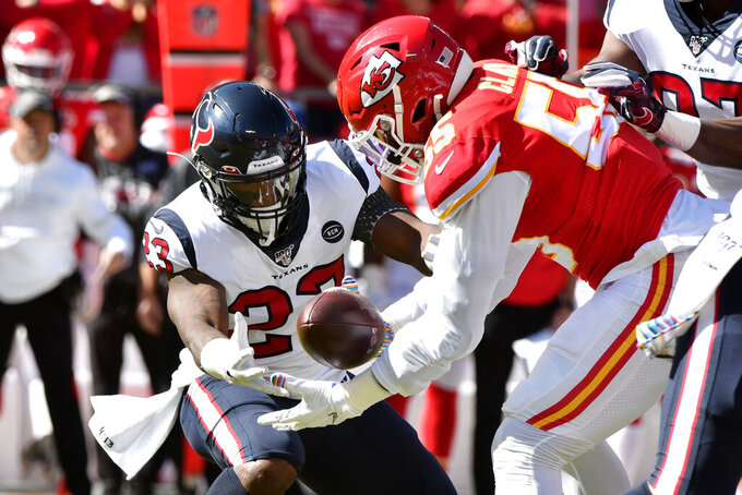Houston Texans running back Carlos Hyde (23) fumbles the ball as Kansas City Chiefs defensive end Frank Clark (55) is about to recover it for a touchdown, during the first half of an NFL football game in Kansas City, Mo., Sunday, Oct. 13, 2019. (AP Photo/Ed Zurga)