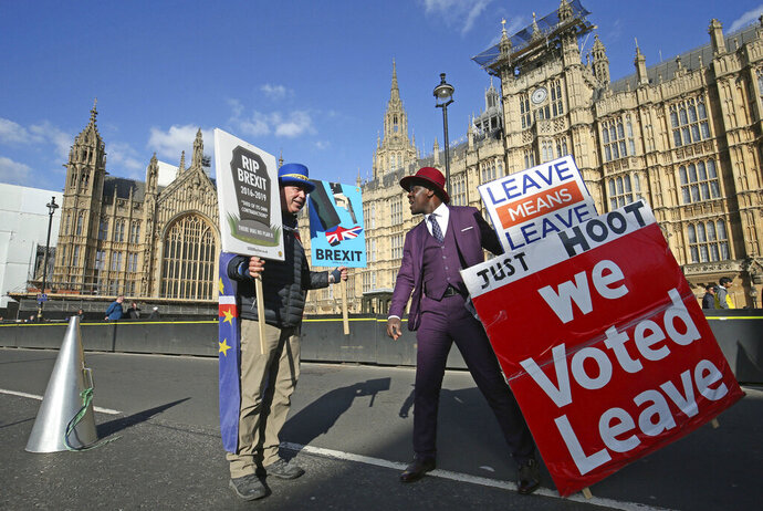 Protestors for opposing views face off against each other, with pro-Brexit split from Europe at right, and pro-Europe anti Brexit at left, outside parliament in London, Monday March 25, 2019. (Jonathan Brady/PA via AP)
