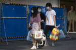 Residents carry their shopping at a retail street in Wuhan in central China's Hubei province on Thursday, April 9, 2020. Released from their apartments after a 2 1/2-month quarantine, residents of the city where the coronavirus pandemic began are cautiously returning to shopping and strolling in the street but say they still go out little and keep children home while they wait for schools to reopen. (AP Photo/Ng Han Guan)