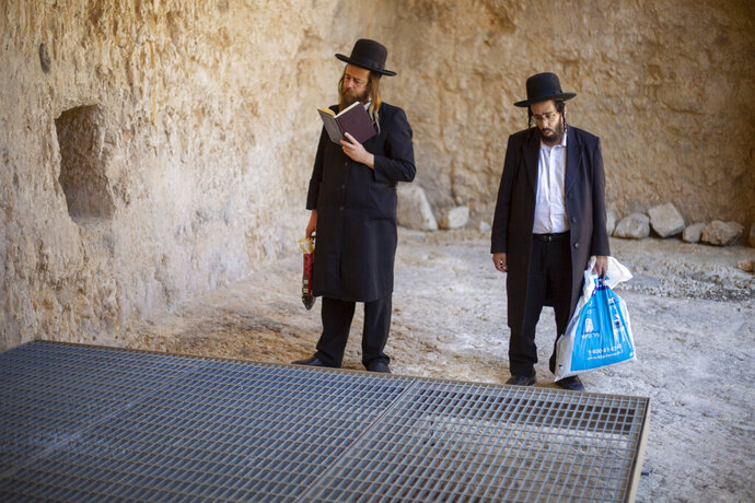 In this Thursday, Oct. 31, 2019 photo, ultra-Orthodox Jews pray in the Tomb of the Kings, a large underground burial complex dating to the first century BC, in east Jerusalem neighborhood of Sheikh Jarrah. After several aborted attempts, the French Consulate General has reopened one of Jerusalem's most magnificent ancient tombs to the public for the first time in over a decade, sparking a distinctly Jerusalem conflict over access to an archaeological-cum-holy site in the volatile city's eastern half. (AP Photo/Ariel Schalit)