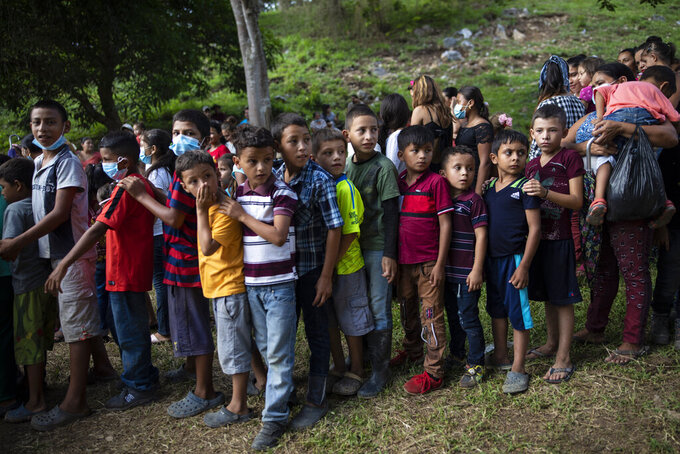 """Children wait in line to receive donated used toys at a ceremony with government officials who arrived to open envelopes containing the bids from companies seeking to build homes for the victims of Hurricane Eta and Iota, in Mission San Francisco de Asis, Honduras, Monday, June 28, 2021.  Friar Leopoldo Serrano, who runs the mission, warned the community to be wary: """"In Honduras we live a daily storm more damaging than hurricanes, the storm of corruption. The authorities deceive us with false promises. That is why I tell you that I still have doubts about the construction of these houses."""" (AP Photo/Rodrigo Abd)"""