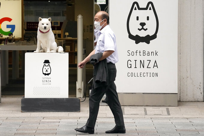 A man walks in front of a SoftBank shop in Tokyo on July 29, 2021. Japanese technology company SoftBank's fiscal first quarter earnings dropped 39% because of the absence of the cash from selling Sprint, which boosted profits a year ago. (AP Photo/Eugene Hoshiko)