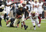 FILE - In this Sept. 22, 2018, file photo, Purdue wide receiver Rondale Moore (4) runs past Boston College defensive back Taj-Amir Torres (24) during the first half of an NCAA college football game in West Lafayette, Ind. No true freshman has ever won the Heisman Trophy, but Moore is performing well enough that he should at least merit consideration for a trip to New York if he keeps up this pace. Purdue visits Michigan State on Saturday.  (AP Photo/Michael Conroy, File)