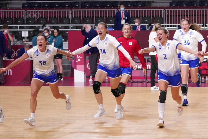 The Russian Olympic Committee's team players celebrate as they won the women's semifinal handball match between Norway and Russian Olympic Committee at the 2020 Summer Olympics, Friday, Aug. 6, 2021, in Tokyo, Japan. (AP Photo/Pavel Golovkin)