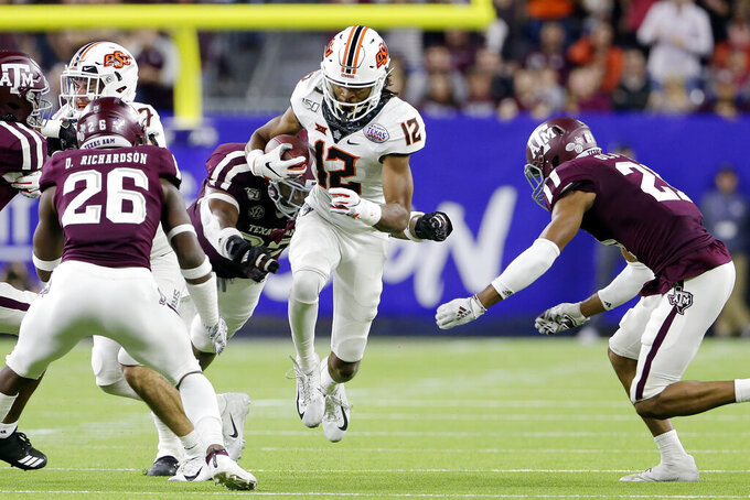Oklahoma State wide receiver Jordan McCray (12) tries to make it through Texas A&M defenders, from left, Demani Richardson (26), Jayden Peevy, back, and Charles Oliver (21) during the second half of the Texas Bowl NCAA college football game Friday, Dec. 27, 2019, in Houston. (AP Photo/Michael Wyke)