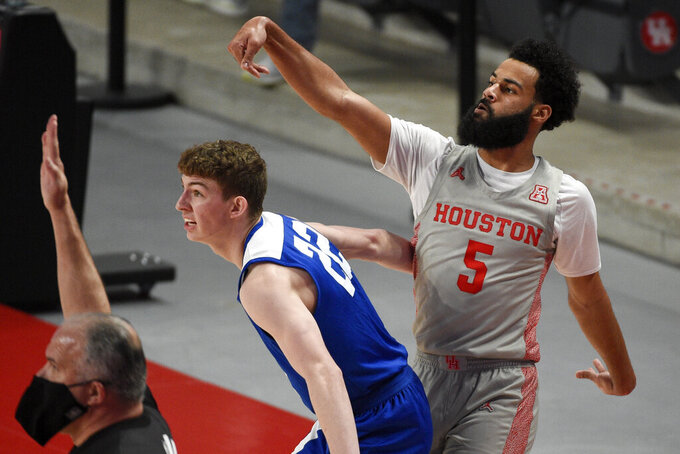 Houston guard Cameron Tyson (5) watches his 3-point basket as Our Lady of the Lake guard Davis Patterson defends during the first half of an NCAA college basketball game, Saturday, Feb. 6, 2021, in Houston. (AP Photo/Eric Christian Smith)