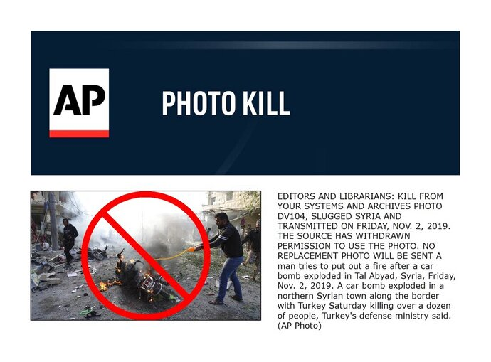 A man tries to put out a fire after a car bomb exploded in Tal Abyad, Syria, Friday, Nov. 2, 2019. A car bomb exploded in a northern Syrian town along the border with Turkey Saturday killing over a dozen of people, Turkey's defense ministry said. (AP Photo)