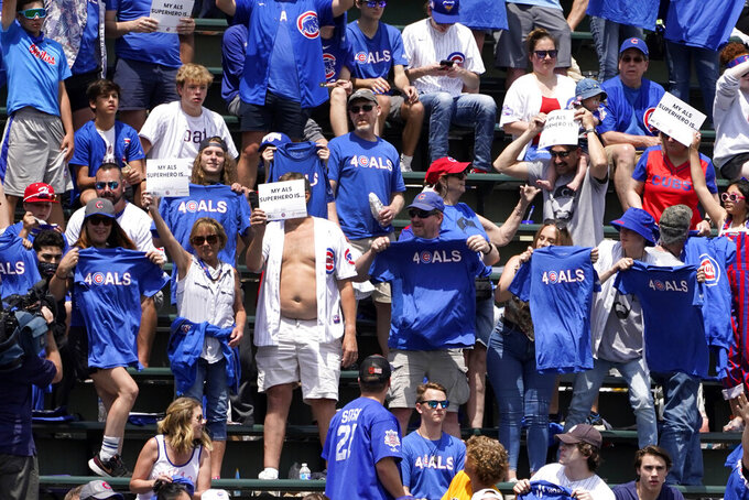 Baseball fans in left field hold up their ALS T-shirts between innings during Lou Gehrig day at Wrigley Field, during a baseball game between the Chicago Cubs and the San Diego Padres, Wednesday, June 2, 2021, in Chicago. (AP Photo/Charles Rex Arbogast)