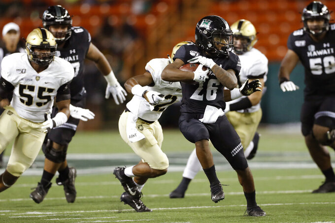 Hawaii running back Miles Reed (26) runs through the Army defense during the first half of an NCAA college football game Saturday, Nov. 30, 2019 in Honolulu. (AP Photo/Marco Garcia)