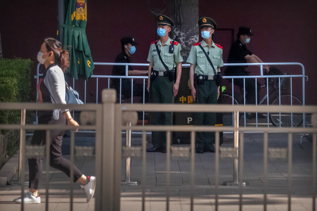 Chinese paramilitary police officers stand guard along a road near Tiananmen Square in Beijing, Thursday, June 4, 2020. China tightened controls over dissidents while pro-democracy activists in Hong Kong and elsewhere sought ways to mark the 31st anniversary Thursday of the crushing of the pro-democracy movement centered on Beijing's Tiananmen Square. (AP Photo/Mark Schiefelbein)