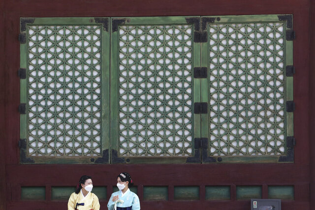 Women wearing face masks to help protect against the spread of the coronavirus talk to each other at the Gyeongbok Palace in Seoul, South Korea, Monday, Aug. 17, 2020. South Korea counted its fourth straight day of triple-digit increases in new coronavirus cases Monday as the government urged people to stay home and curb travel. (AP Photo/Ahn Young-joon)