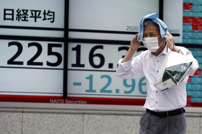 A man walks in the rain past an electronic stock board showing Japan's Nikkei 225 index at a securities firm in Tokyo Friday, July 10, 2020. Asian stock markets followed Wall Street lower Friday on worries economic improvements might fade as coronavirus cases increase in the United States and some other countries. (AP Photo/Eugene Hoshiko)