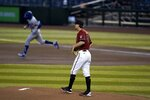 Arizona Diamondbacks starting pitcher Taylor Clarke, right, pauses on the mound after giving up a home run to Los Angeles Dodgers right fielder Mookie Betts, left, during the first inning of a baseball game Wednesday, Sept. 9, 2020, in Phoenix. (AP Photo/Ross D. Franklin)