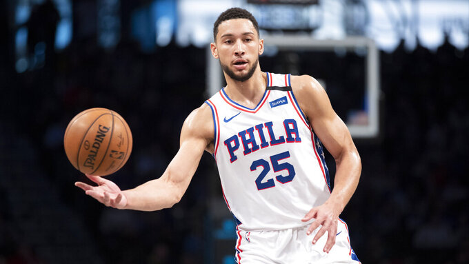 FILE - In this  Monday, Jan. 20, 2020 file photo, Philadelphia 76ers guard Ben Simmons moves the ball during the first half of an NBA basketball game against the Brooklyn Nets in New York. All-Star guard Ben Simmons says he's feeling strong in his recovery from a lower back injury and expects to be at full strength once the NBA season resumes. Simmons, who averaged 16.7 points, 7.8 rebounds and 8.2 assists in 54 games, was hurt in a Feb. 22 game at Milwaukee. (AP Photo/Mary Altaffer, File)