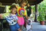 From left, Omar Brooks, and his daughters Zaida Brooks, 5, and Waverly Brooks, 2, pet Maisie Mae, a foster dog at Bridge To Home Animal Rescue on Monday, July 6, 2020, in Eighty Four, Pa. Brooks and his family have been fostering dogs for the past two years. (Andrew Rush/Pittsburgh Post-Gazette via AP)