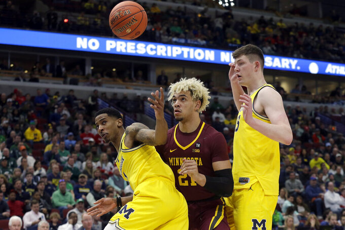 Michigan's Charles Matthews (1), Minnesota's Jarvis Omersa (21) and Michigan's Jon Teske (15) look attitude the loose ball during the second half of an NCAA college basketball game in the semifinals of the Big Ten Conference tournament, Saturday, March 16, 2019, in Chicago. (AP Photo/Kiichiro Sato)