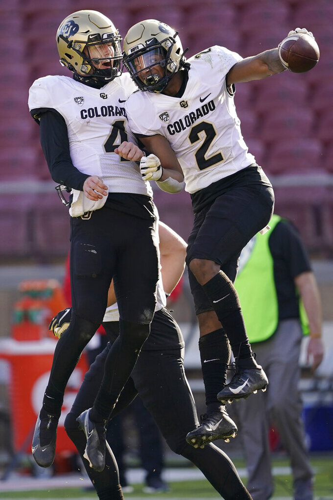 FILE - In this Saturday, Nov. 14, 2020, file photo, Colorado quarterback Sam Noyer (4) and wide receiver Brenden Rice (2) celebrate after connecting on a touchdown pass against Stanford during the second half of an NCAA college football game in Stanford, Calif. Brenden Rice is following in the footsteps of his father, NFL standout Jerry Rice, by playing as a wide receiver for the Colorado Buffaloes during this coronavirus-shortened season. (AP Photo/Jeff Chiu, File)