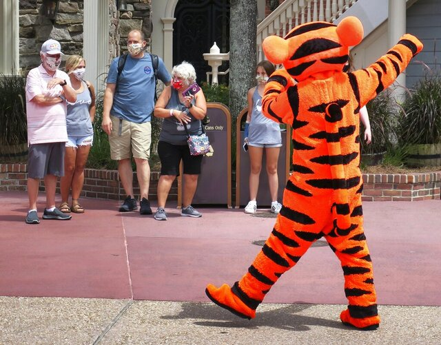 FILE- In this July 11, 2020 file photo, Tigger entertains guests wearing masks as required to attend the official reopening day of the Magic Kingdom at Walt Disney World in Lake Buena Vista, Fla. Walt Disney World announced Wednesday, Oct. 28, 2020, that over 700 actors and singers will be laid off. (Joe Burbank/Orlando Sentinel via AP, File)
