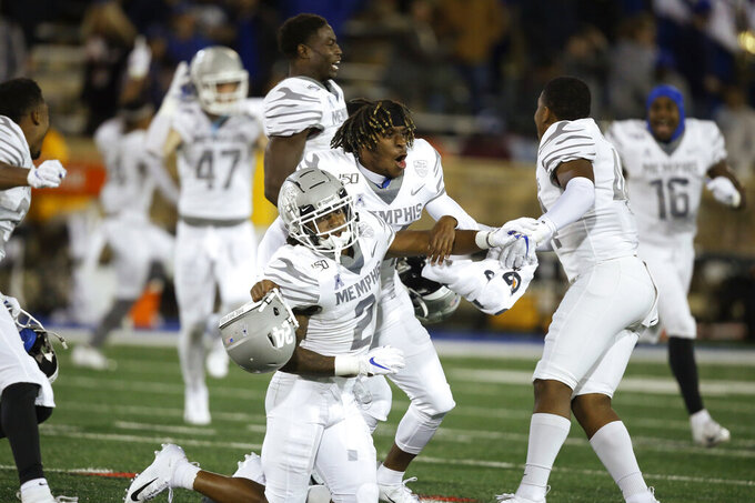 Memphis players T.J. Carter (2), Cameron Fleming, center, and Kendell Johnson, right, celebrate at the end of the game after defeating Tulsa 42-41 in an NCAA college football game in Tulsa, Okla., Saturday, Oct. 26, 2019. (AP Photo/Sue Ogrocki)