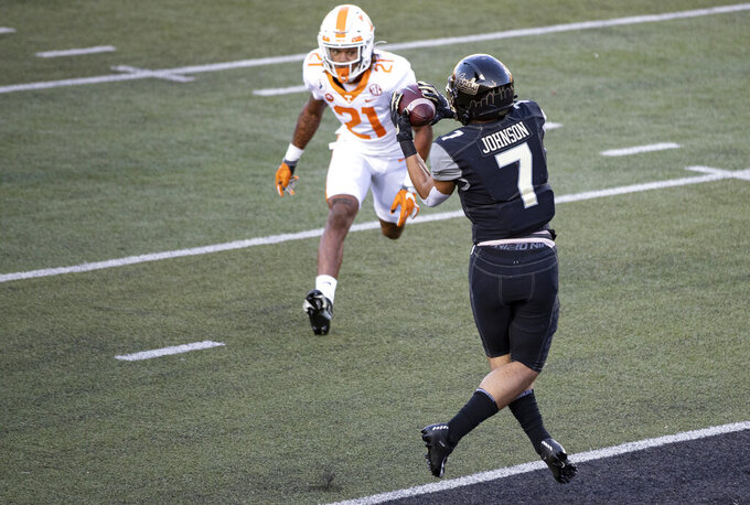 Vanderbilt wide receiver Cam Johnson (7) catches a pass for a touchdown in front of Tennessee defensive back Tamarion McDonald (21) during the first half of an NCAA college football game Saturday, Dec. 12, 2020, in Nashville, Tenn. (AP Photo/Wade Payne)