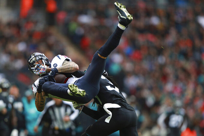 Jacksonville Jaguars cornerback Tre Herndon (37) hits Houston Texans wide receiver Kenny Stills (12) during the first half of an NFL football game at Wembley Stadium, Sunday, Nov. 3, 2019, in London. (AP Photo/Ian Walton)