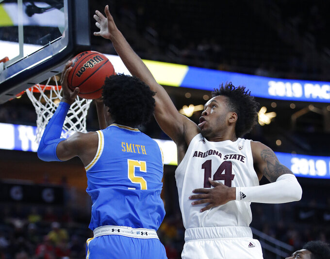 Arizona State's Kimani Lawrence, right, blocks a shot by UCLA's Chris Smith during the first half of an NCAA college basketball game in the quarterfinals of the Pac-12 men's tournament Thursday, March 14, 2019, in Las Vegas. (AP Photo/John Locher)