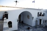 A woman crawls as other pilgrims sit at the yard of the Holy Church of Panagia of Tinos, on the Aegean island of Tinos, Greece, on Thursday, Aug. 13, 2020. For nearly 200 years, Greek Orthodox faithful have flocked to Tinos for the August 15 feast day of the Assumption of the Virgin Mary, the most revered religious holiday in the Orthodox calendar after Easter. But this year there was no procession, the ceremony _ like so many lives across the globe _ upended by the coronavirus pandemic. (AP Photo/Thanassis Stavrakis)