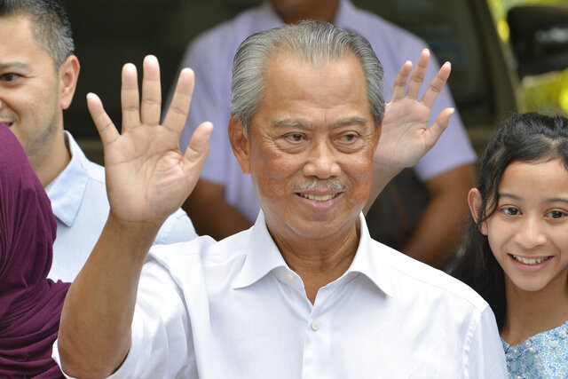 Politician Muhyiddin Yassin, center, waves to media after outside his house after he being appointed as the new prime minister in Kuala Lumpur, Malaysia, Saturday, Feb. 29, 2020. Malaysia's king has appointed seasoned politician Muhyiddin Yassin as the new prime minister, trumping Mahathir Mohamad's bid to return to power after a week of political turmoil that followed his resignation as prime minister. (AP Photo/John Shen Lee)
