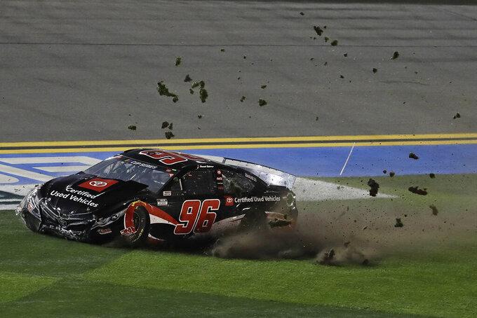 Daniel Suarez's car kicks up grass as it slide across the infield after a crashing with Ryan Blaney's car during a NASCAR Daytona 500 qualifying auto race Thursday, Feb. 13, 2020, at Daytona International Speedway in Daytona Beach, Fla. (AP Photo/Chris O'Meara)