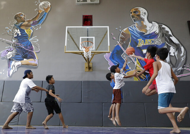 Boys plays beside images of former NBA basketball player Kobe Bryant at the