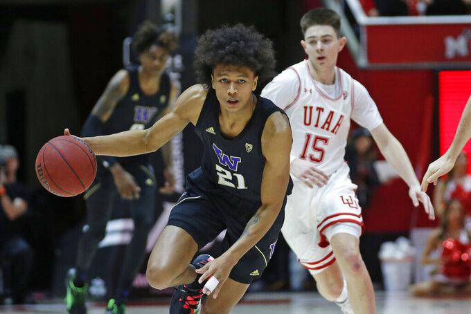 Washington forward RaeQuan Battle (21) brings the ball up court as Utah guard Rylan Jones (15) defends in the first half during an NCAA college basketball game Thursday, Jan. 23, 2020, in Salt Lake City. (AP Photo/Rick Bowmer)